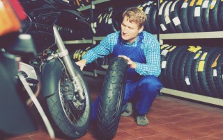 Cheerful working man standing with new tires for motorbike in hands in shop