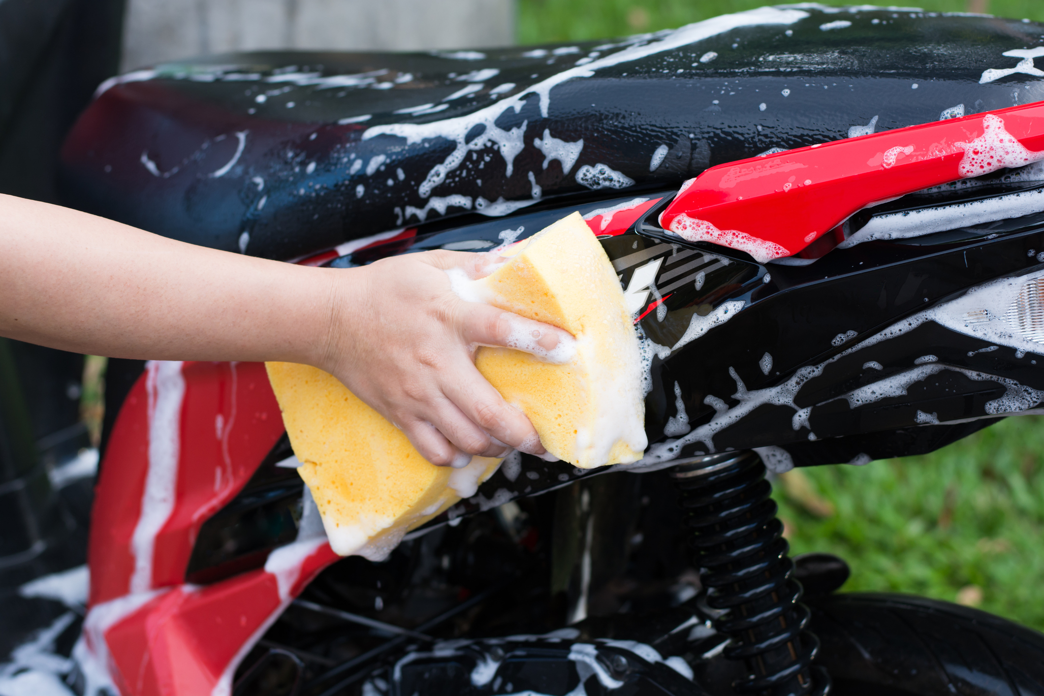 Female hand with  yellow sponge  washing a motorcycle.